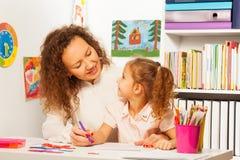 Kleines hörendes Schulmädchen ihr Lehrer an der Lektion Lizenzfreie Stockfotos