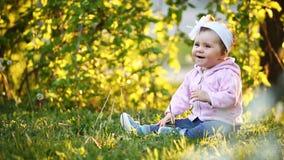 Kleines hübsches Baby, das auf grünem Gras im Park bei dem Sonnenuntergang sitzt stock video footage