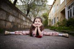 Kleines hübsches Mädchen, das draußen Spalten tut Stockfoto