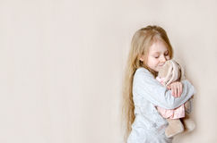 Kleines hübsches Mädchen, das ihr Spielzeugkaninchen umarmt Stockbilder