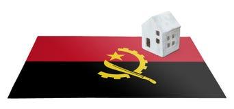 Kleines Haus auf einer Flagge - Angola Stockfotos