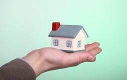 Kleines Haus in der Hand auf grünem Hintergrund Stockfotografie