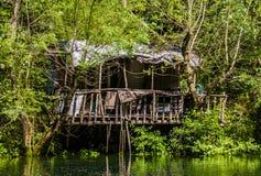 Kleines Haus durch den See Stockbild