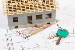 Kleines Haus im Bau, Schlüssel und Währungen Euro auf elektrischen Zeichnungen für Projekt, errichtendes Hauptkostenkonzept Lizenzfreie Stockbilder