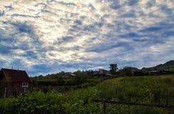 Kleines Haus im Dorf, dunkle Wolken auf einem blauen Himmel und grünes Gras im Tal eines Berges Lizenzfreie Stockbilder