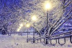 Kleines Haus im Schnee deckte Holz in den Schweizer Alpen ab Schneefälle im Nachtpark mit Laternen Abstraktes Hintergrundmuster d Stockfoto