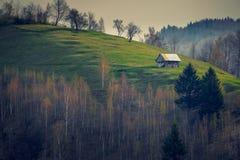 Kleines Haus lokalisiert auf einem Hügel mit einigen Bäumen im Vordergrundschuß nach Sonnenaufgang gegen einen bewölkten Himmel lizenzfreies stockfoto