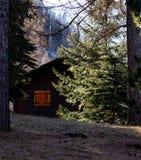 Kleines Haus mit orange Fenster im Wald lizenzfreie stockbilder