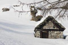 Kleines Haus und Baum auf den Alpen Lizenzfreies Stockbild