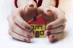 Kleines Haus zwischen Händen Lizenzfreie Stockbilder