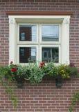 Kleines hellgelbes quadratisches Fenster auf einer Backsteinmauer Lizenzfreie Stockfotografie