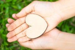 Kleines Herz in den Händen der Frauen auf natürlichem Hintergrund stockfoto