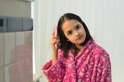 Kleines hispanisches Mädchen, das ihr Haar aufträgt Stockbild
