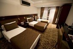 Kleines Hotelzimmer mit drei einzelnen Betten stockfotografie