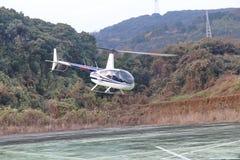 Kleines Hubschrauberfliegen über dem Grund, Berg habend, wie zurück gerieben Stockfoto