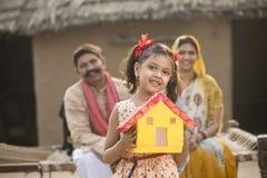 Kleines indisches Mädchen, das Traumhausmodell hält stockfoto