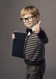 Kleines intelligentes Kind des Jungen in den Gläsern, die Zertifikat der leeren Karte zeigen Stockfotos