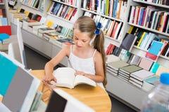 Kleines intelligentes Mädchen, das ein Buch in der Schulbibliothek liest Lizenzfreie Stockbilder