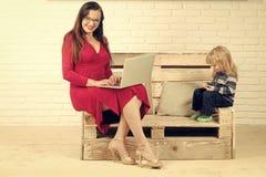 Kleines Jungen- und Lehrermädchen in den Gläsern, blogging Stockfotografie