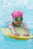 Kleines junges Mädchen, das Schwimmen in einem Pool lernt stockbilder