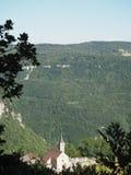 Kleines Jura-Dorf zwischen zwei Bergen stockfotografie