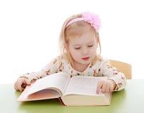 Kleines kaukasisches blondes Mädchen, das an einem Schreibtisch sitzt und Lizenzfreies Stockbild