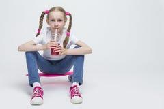 Kleines kaukasisches blondes Mädchen, das mit rosa Pennyboard aufwirft Lizenzfreies Stockfoto