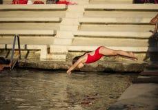 Kleines kaukasisches Mädchen, das in das Meer springt Lizenzfreies Stockfoto