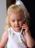 Kleines kaukasisches Mädchen, das zum Handy hört Stockfoto