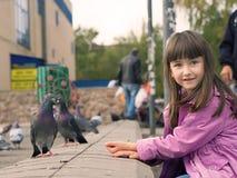 Kleines kaukasisches Mädchen und Tauben Stockfoto