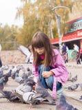 Kleines kaukasisches Mädchen und Tauben stockfotografie