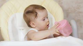 Kleines Kind aß Kartoffelpürees und trinkt Wasser von einem rosa Glas stock video