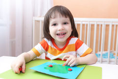 Kleines Kind, das Apfelbaum von playdough modelliert Lizenzfreie Stockfotografie
