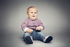 Kleines Kind, das auf dem Boden, lächelnd sitzt Lizenzfreies Stockfoto