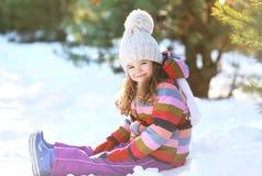 Kleines Kind, das auf dem Schnee hat Spaß im Winter sitzt Stockfoto