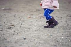 Kleines Kind, das auf den Sand am Winterstrand geht Stockfotografie