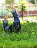 Kleines Kind, das auf einem grünen Rasen liegt Stockbilder