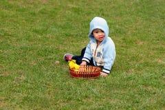 Kleines Kind, das auf einem grünen Wiesengras sitzt Stockfotos