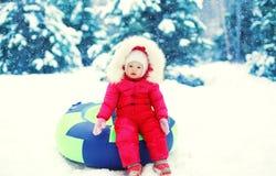 Kleines Kind, das auf Schlitten im Winter sitzt Stockfoto