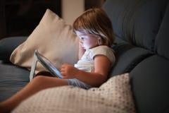 Kleines Kind, das bequem in aufpassender Tablette des Sofas sitzt lizenzfreies stockfoto