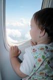 Kleines Kind, das durch das Fenster des Flugzeuges schaut Stockfotos