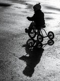 Kleines Kind, das ein Dreirad reitet Lizenzfreie Stockfotos