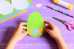 Kleines Kind, das eine Ostern-Karte in den Händen hält Kind machte Ostern-Grußkarte in der Eiform lizenzfreies stockfoto