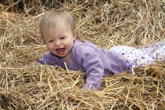 Kleines Kind, das in einem Stapel des Strohs lacht Lizenzfreie Stockbilder