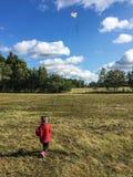 Kleines Kind, das einen Drachen auf einem windigen Feld fliegt stockfoto