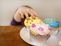Kleines Kind, das einen Kuchen schleicht Stockfoto