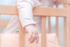 Kleines Kind, das in einer Krippe steht Stockfotos