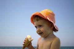 Kleines Kind, das Eiscreme auf dem Strand isst Lizenzfreie Stockfotografie