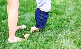 Kleines Kind, das erste Schritte auf grünem Gras tut Beine der jungen Mutter und ihres Babysohns Stockbilder
