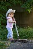 Kleines Kind, das herauf Boden harkt und für das Pflanzen sich vorbereitet Stockfotos